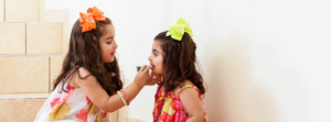 little girls applying lipstick