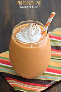 Glass with orange stripped straw filled with pumpkin pie smoothie and whipped cream