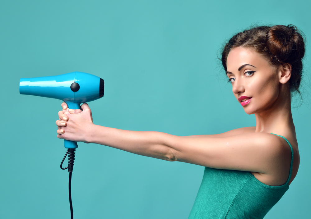 a girl using a hair dryer like a gun