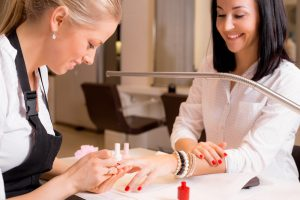 Blond woman applying red nail polish to nail salon client with bracelets