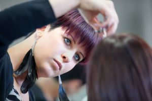 Makeup artist with purple hair and feather earrings applying makeup to client