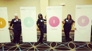 Three women in black at trade show near banners that spell out hair