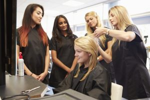 Four cosmetology students learning with one woman in salon chair