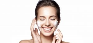 Smiling woman with perfect skin hair back with foam cleanser on her face.