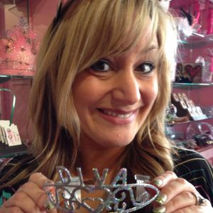Blond woman smiling holding a tiara that reads DIVA