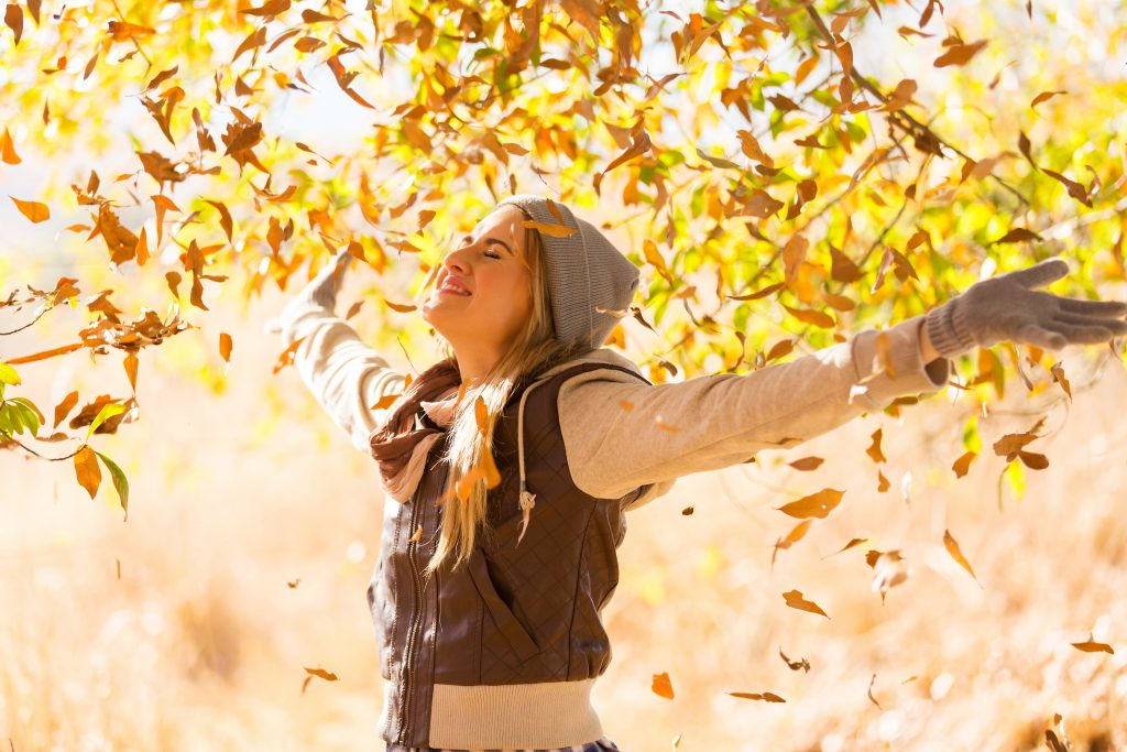 Smiling woman standing arms outstretched under autumn fall trees