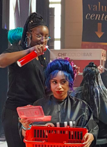 Woman spraying hairspray on salon client with bue hair updo style