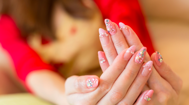 Woman holding her hands up to see beautiful pink manicure with gems and pearls.