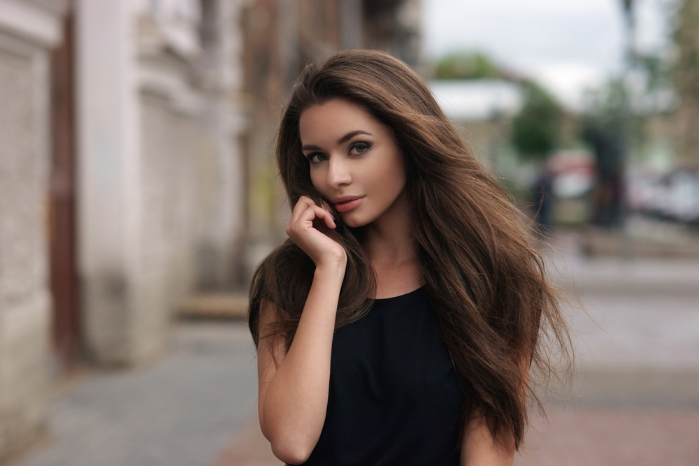 Young beautiful woman on street with long brown hair and black shirt