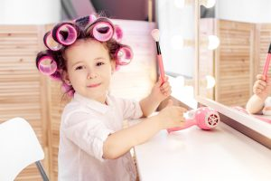 Young girl with hair in curlers smiling holding a makeup brush