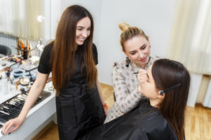 Students learning about makeup application