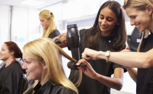 Blonde woman instructing brunette woman holding hairdryer and round brush styling a blonde woman's hair