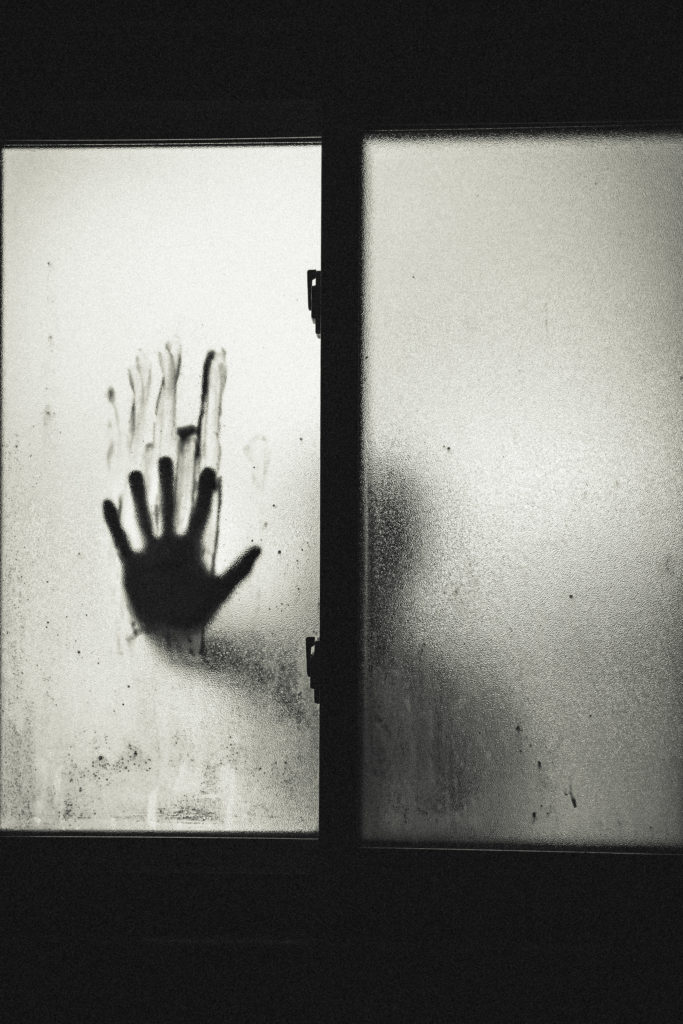 Fuzzy black and white image of hand on window smudging blood