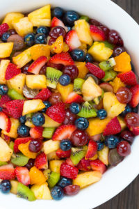 Bowl filled with fruit salad of slices strawberries kiwis red grapes pineapple blueberries and oranges