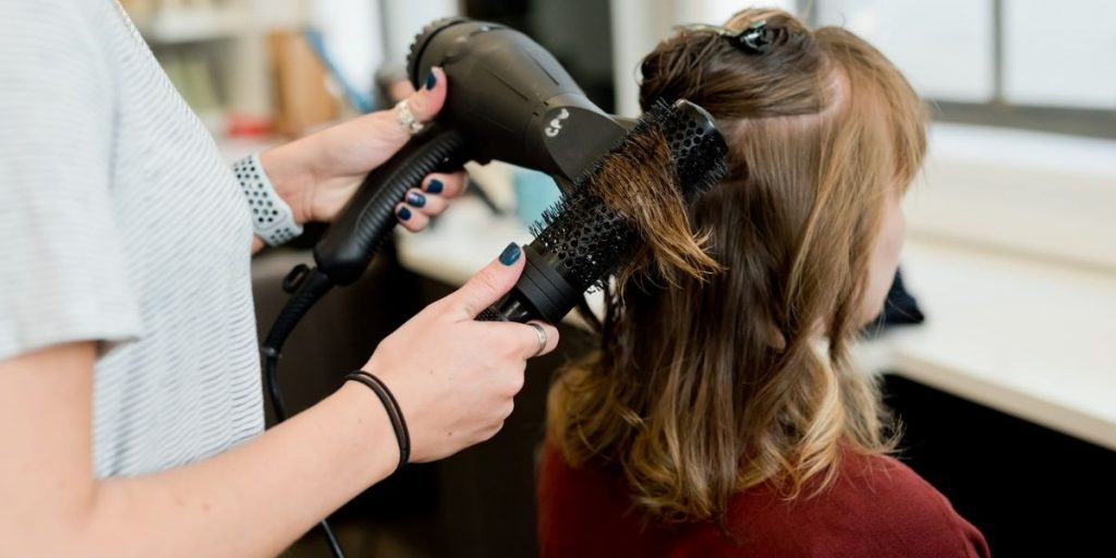 woman getting her hair styled at the salon