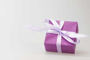 Purple gift box wrapped in light lavender bow with white background