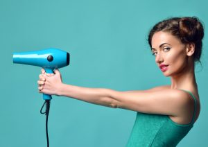 Girl in turquoise shirt holding a hair dryer like a gun with her hair in buns