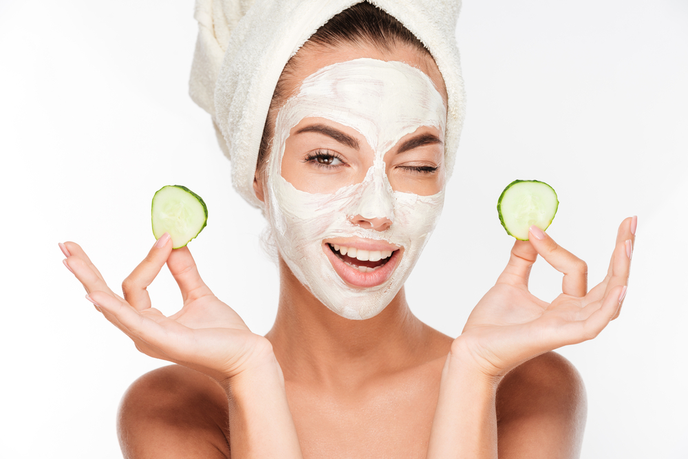 Girl in beauty face mask with white towel on her head holding up cucumber slices