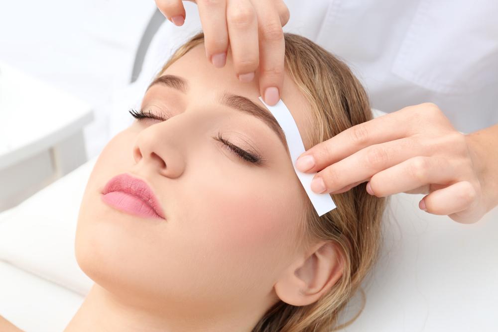 esthetician waxing an eyebrow