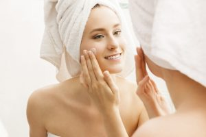 Woman applying skincare product to face with hair in a towel