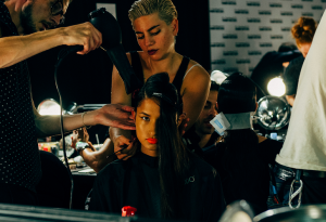 Hair model surrounded by stylists preparing her hair in front of mirror