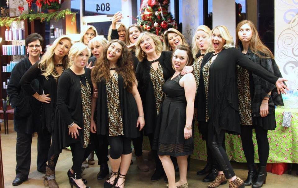 Group of fourteen women dressed in black and leopard print making silly expressions