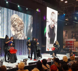 Image of models and hairstylists on stage with onlookers