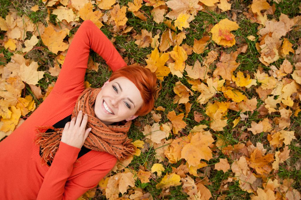 Smiling redheaded woman laying in colored fall leaves wearing a scarf