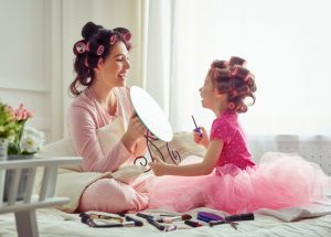 Mother and daughter sitting on bed facing each other smiling both with hair in curlers playing with makeup