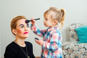 Blonde child giving her mother a makeover with makeup brush