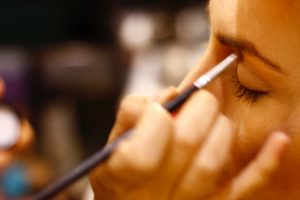 Close up of woman applying eyeshadow with a brush on a customer
