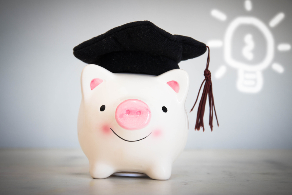 pink and white piggy bank with graduate cap