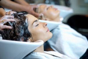 People getting their hair shampoos at a salon