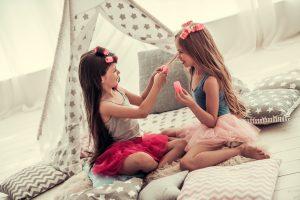 two little girls doing hair