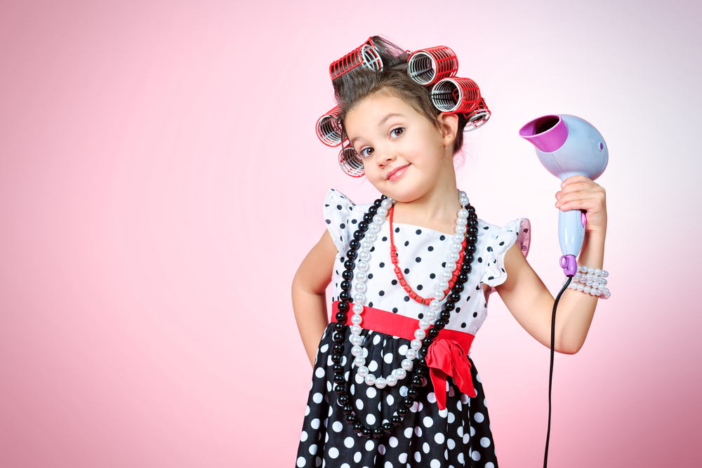 little girl with curlers in her hair holding a hairdryer
