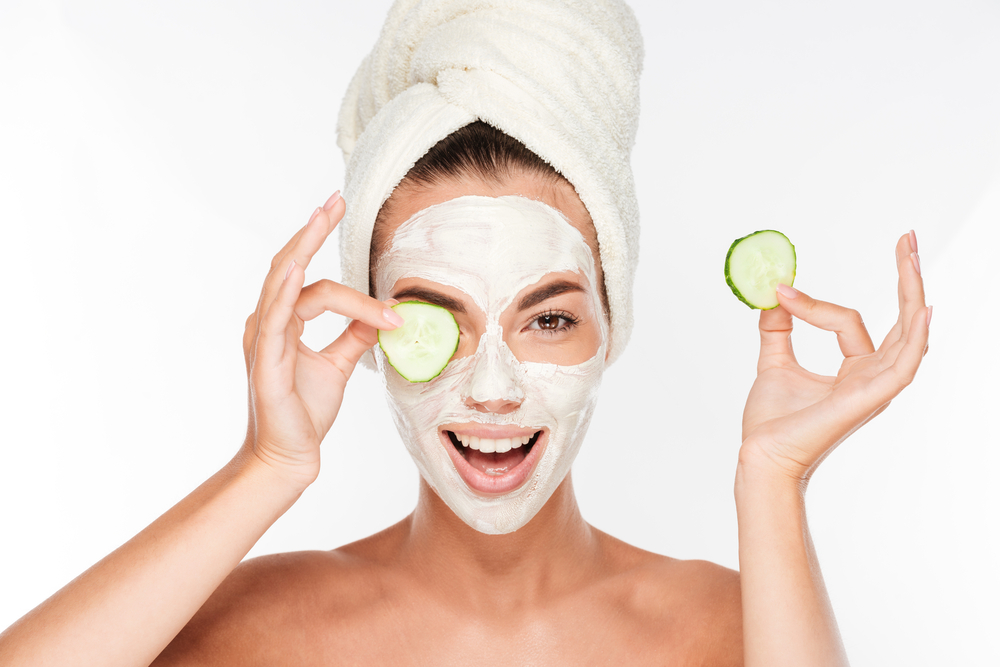 Woman with face mask holding a cucumber