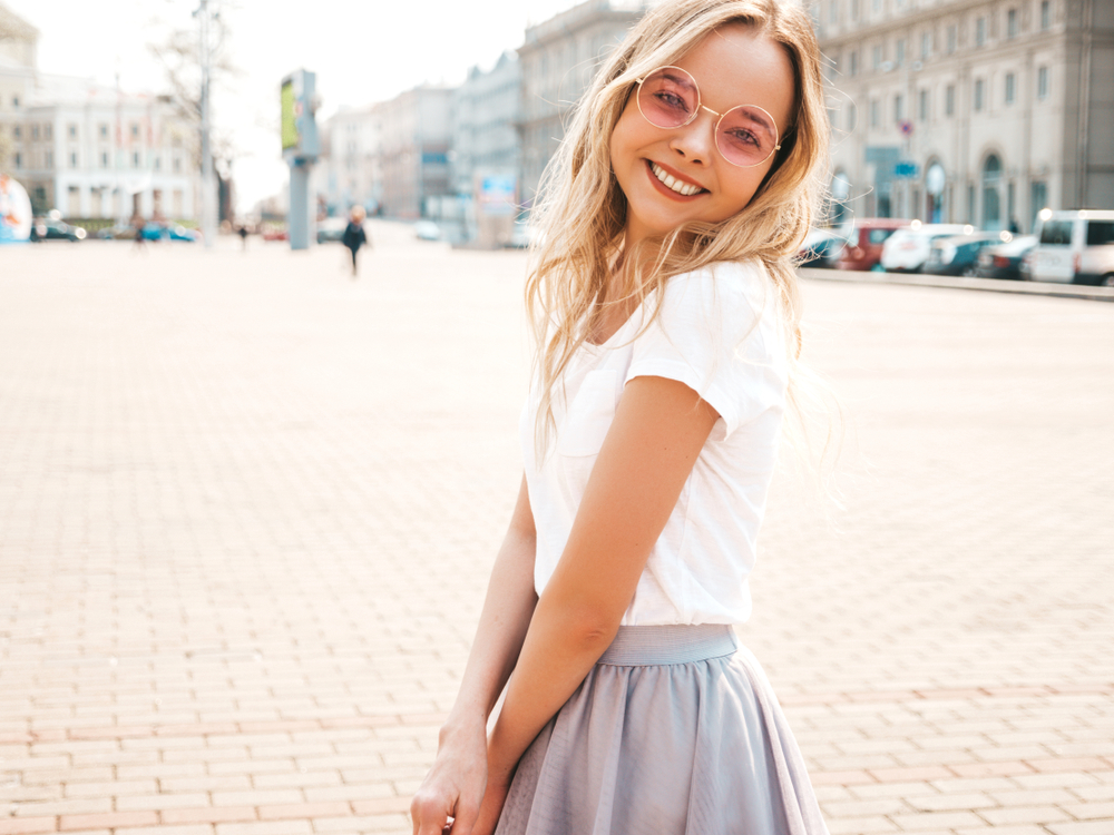 blonde girl wearing pink sunglasses and smiling
