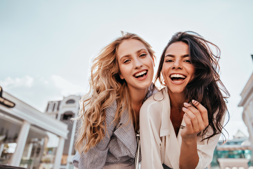 two girls laughing and looking at camera