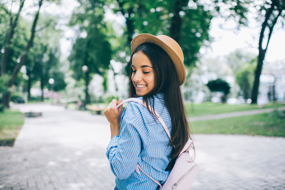 brunette wearing straw hat and small pink backpack