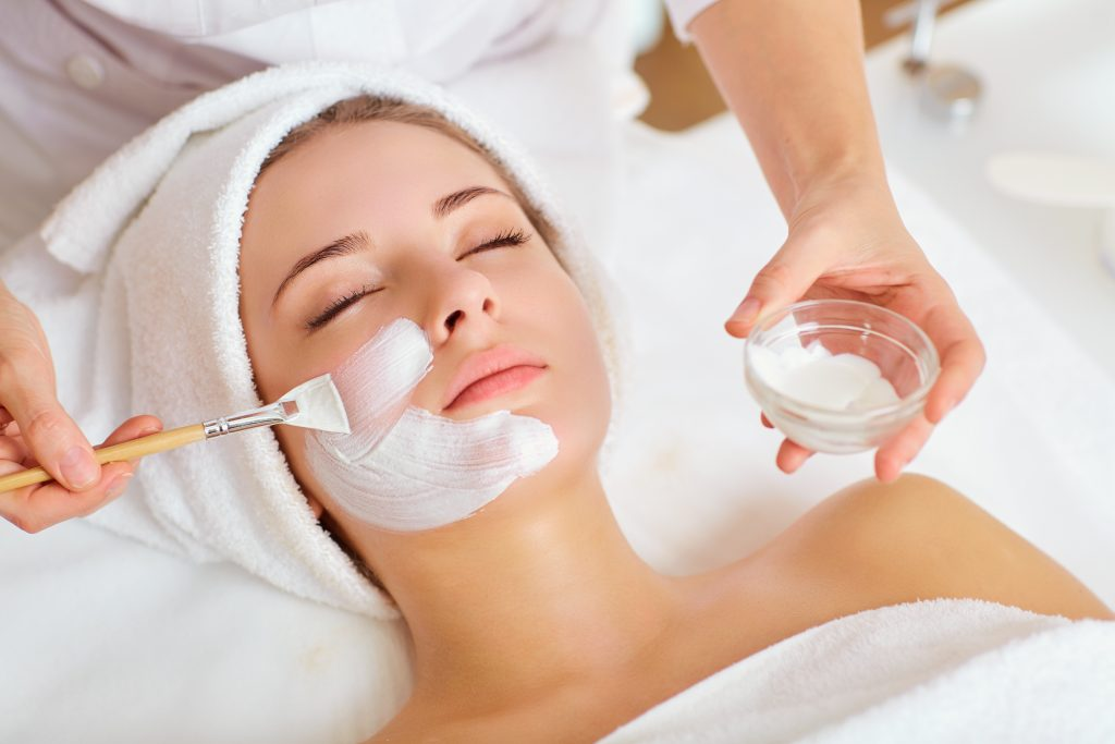 young woman getting a facial in a spa