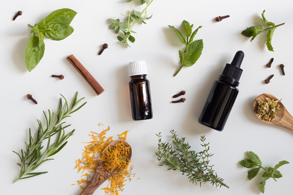 essential oils wth a selection of herbs on white background