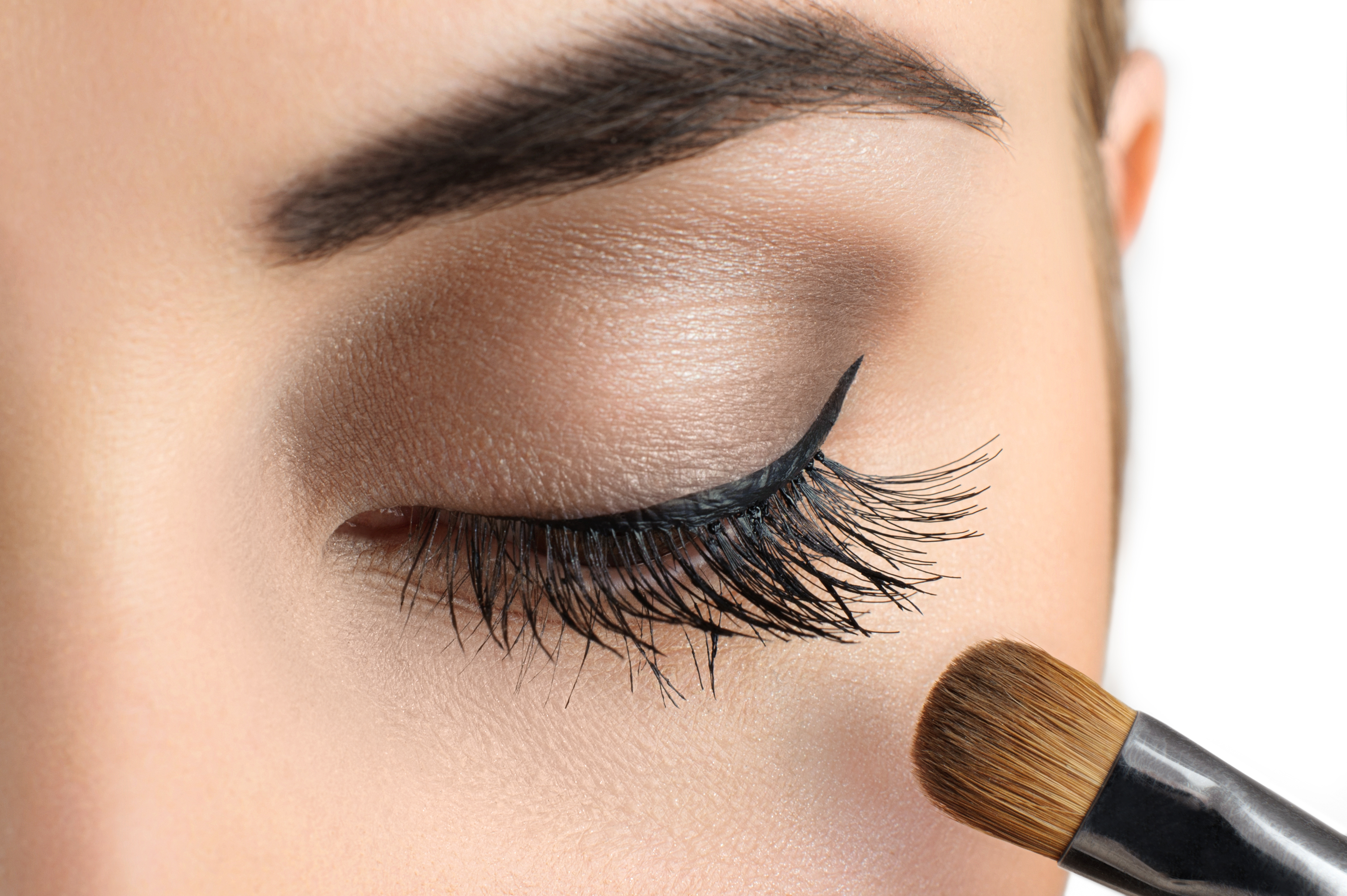 flat eyeshadow brush in front eyelashes of a woman with her makeup done