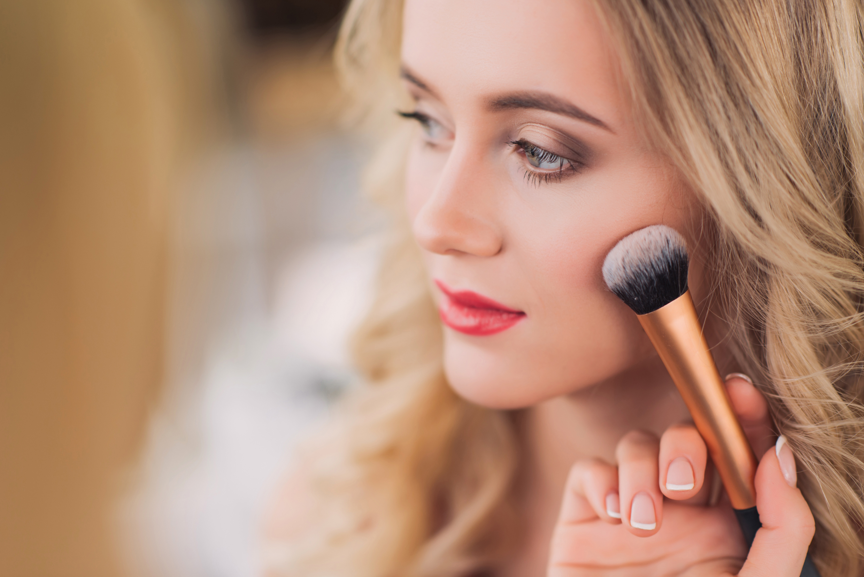 a makeup artist using a blush brush on a female client