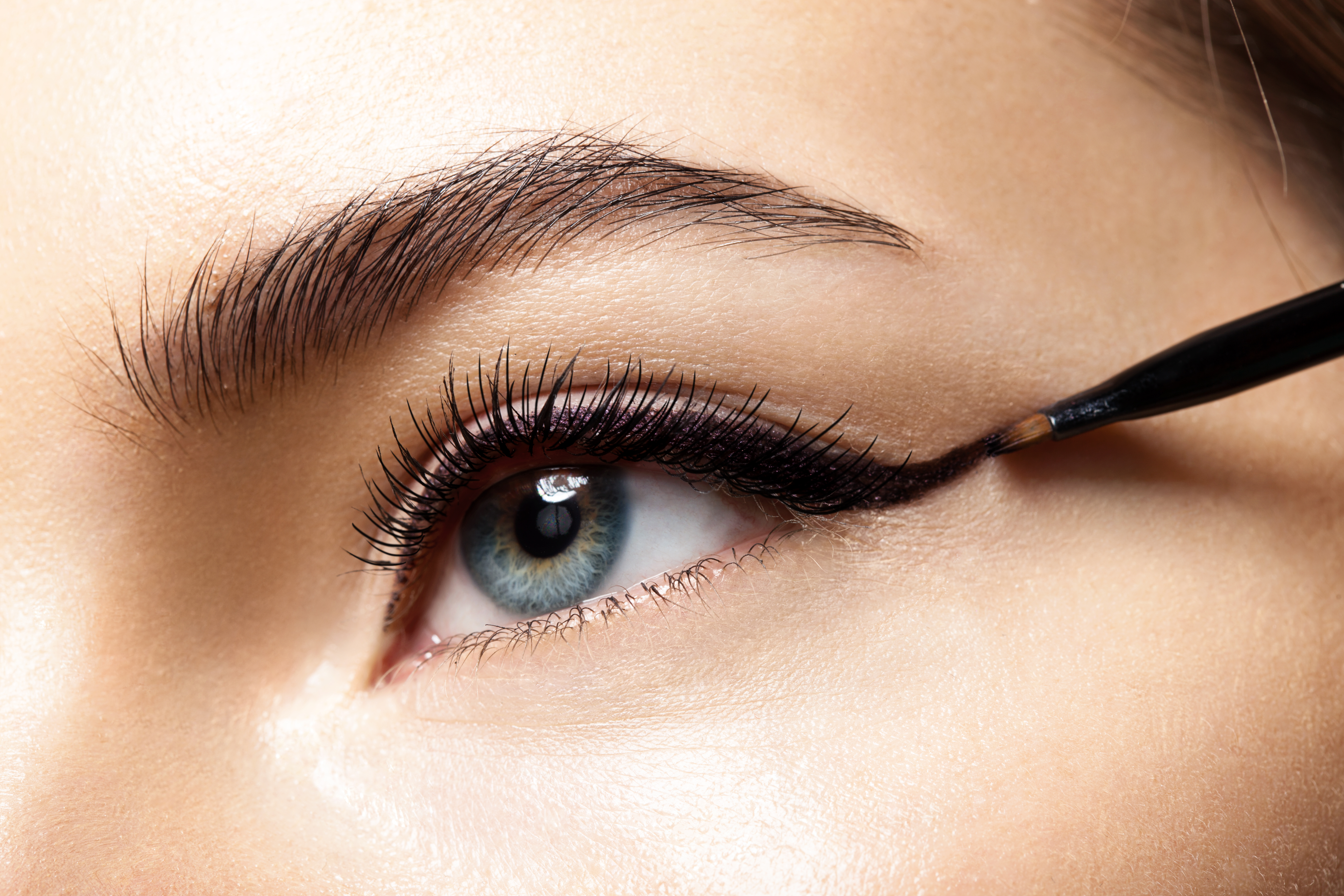 closeup of an eyeliner brush being used on a woman to create a perfect wing