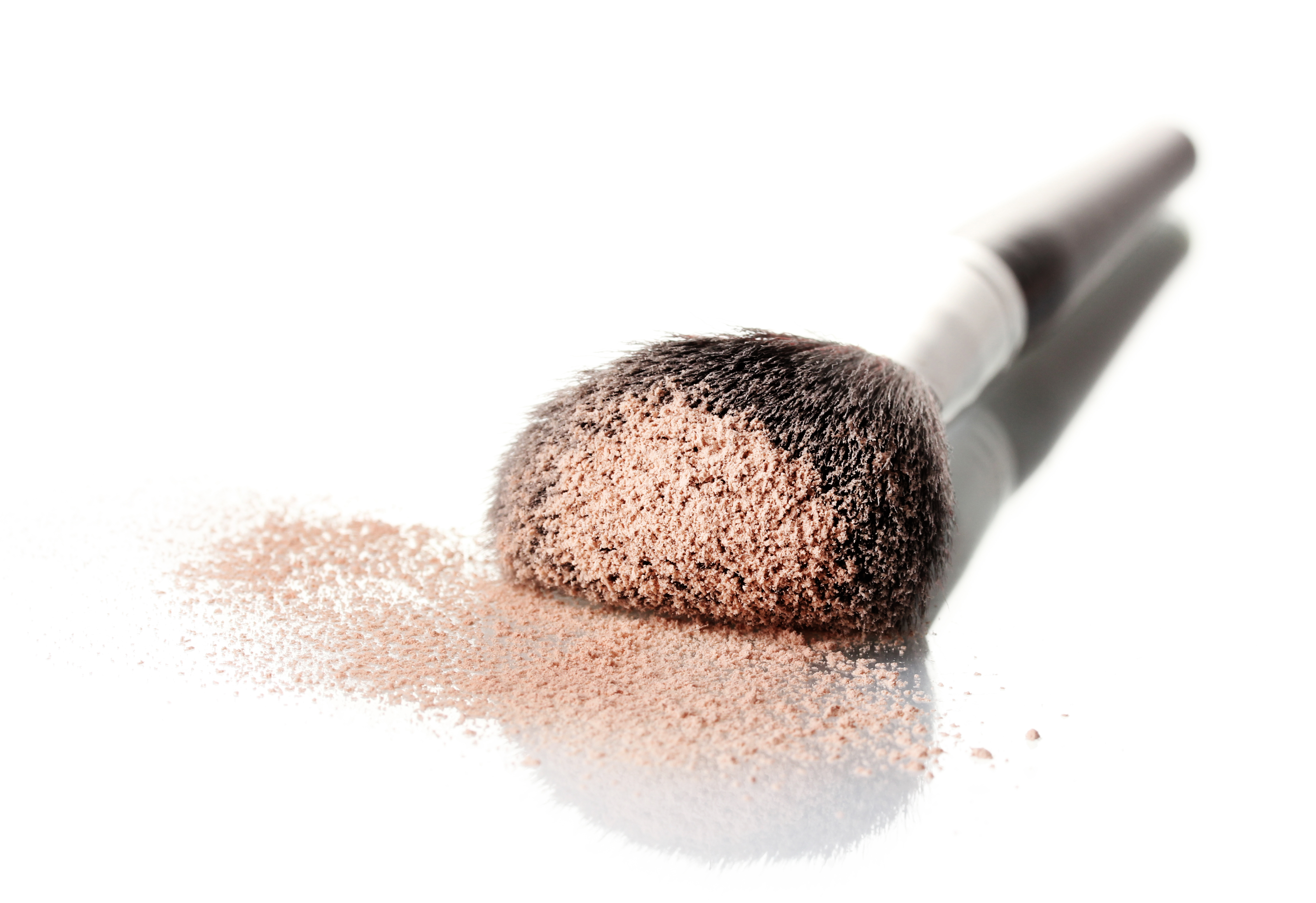 a powder brush laying on a table with a bunch of extra product on the brush and table