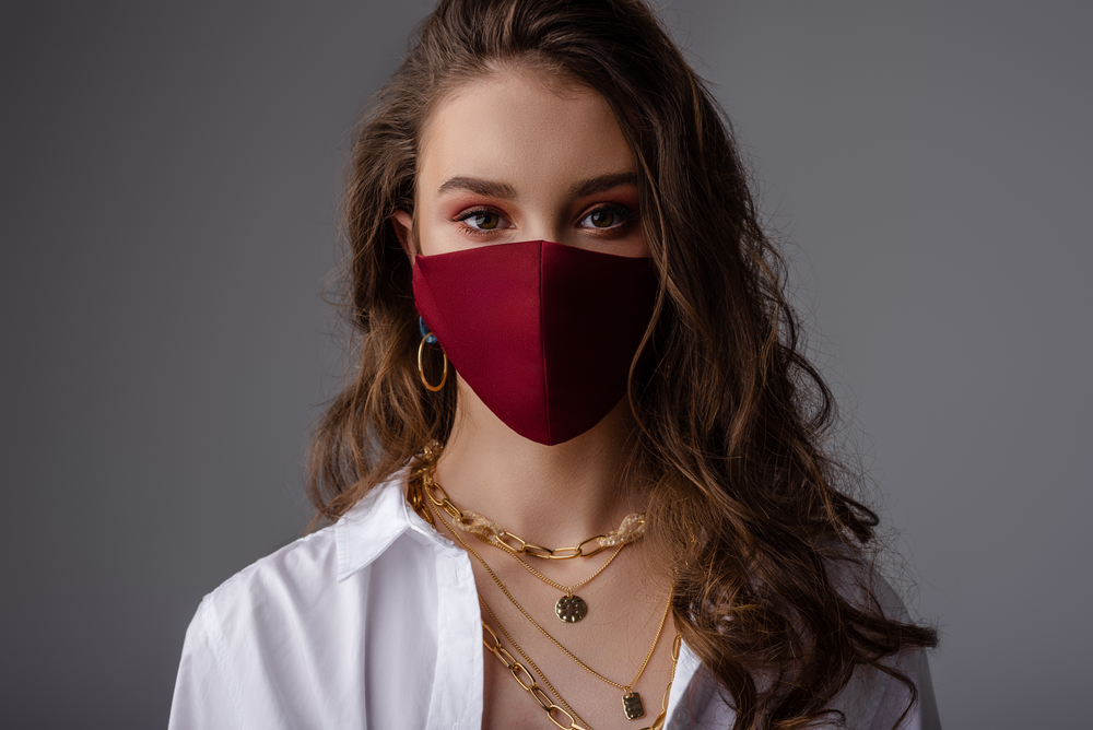 young woman modeling a facemask with red eyeshadow and gold jewelry with white shirt