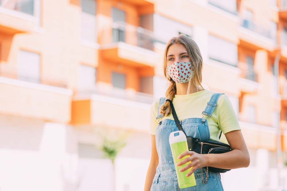 girl holding a water bottle as she's walking with a face mask on.