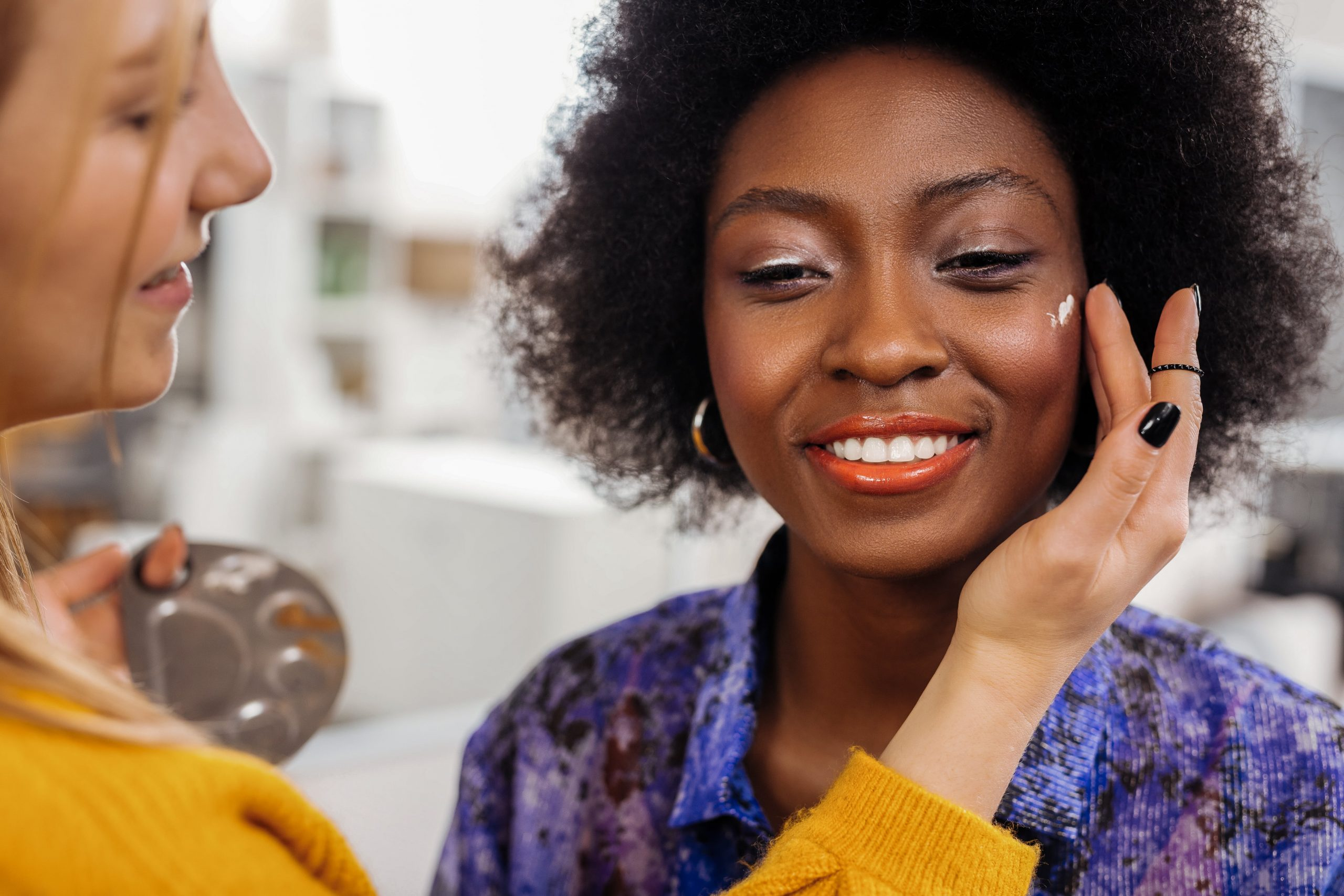 woman smiling while she gets her makeup done