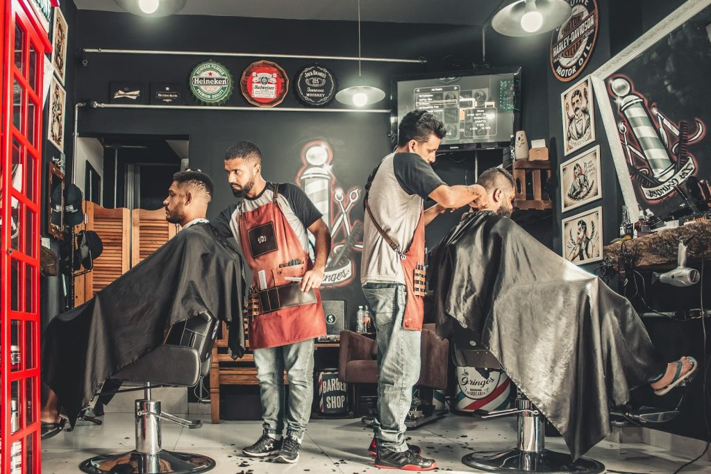 Two barbers working in a barber shop